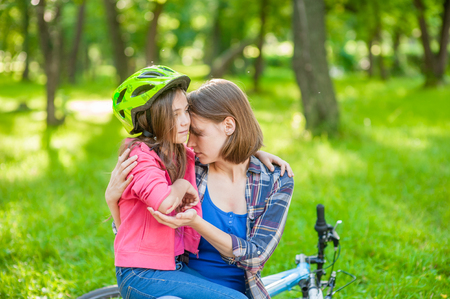 mom calms daughter who fell off her bike.