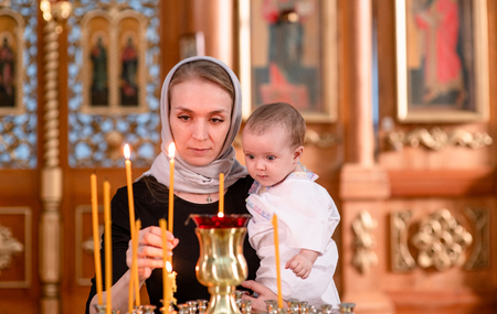 a woman with a baby puts a candle in church.