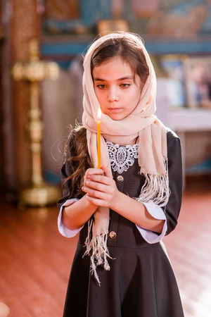 Little girl with a candle standing in the church and prays.