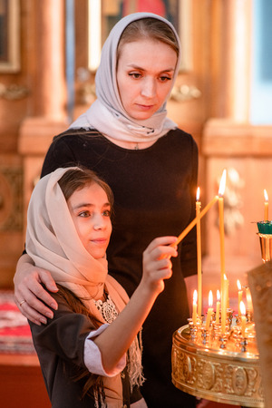 Young mother and little girl sets fire to a candle in the church before the prayer. Stock Photo
