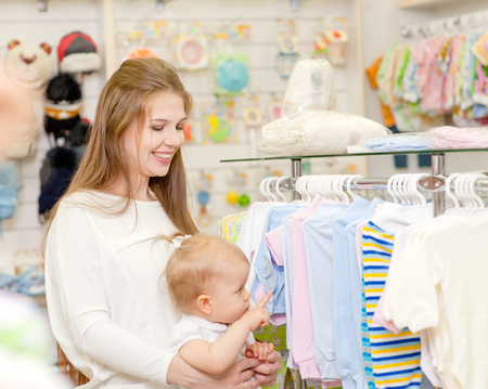 Pregnant woman with a small child choose baby clothes in the store. Standard-Bild
