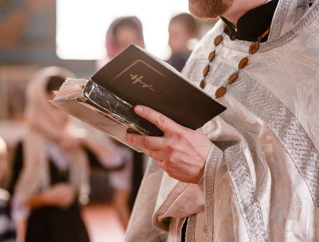 Closeup priest reads bible during church ceremony.