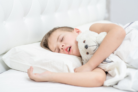Young boy with toy bear is sleeping with his mouth open, snoring. Banque d'images