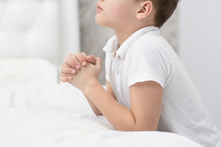 Close up young boy praying at home before bedtime. Stok Fotoğraf