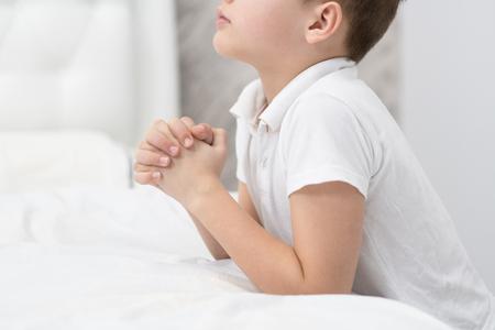 Gros plan sur un jeune garçon priant à la maison avant de se coucher.