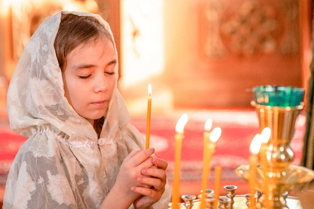 little girl with eye closed holds a candle and prays in church.