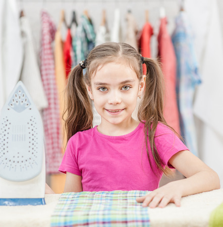 Smiling little girl is leaning on ironing board at home.