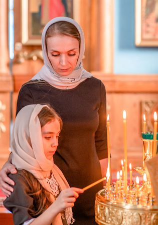 Mother and little girl holds candle in the church and prays.
