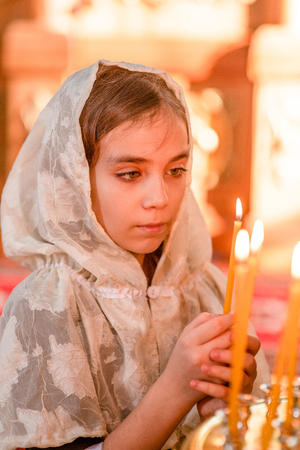 Sad girl with candle in church.
