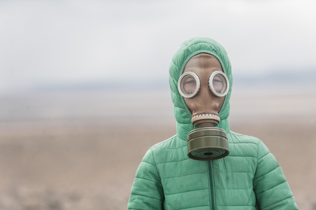 Kid in a gas mask on a deserted field. Apocalypse postnuclear Doomsday scenario. Imagens