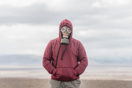 Alone man in a gas mask on a deserted field. Apocalypse postnuclear Doomsday scenario. Imagens