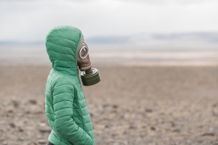 Kid in a gas mask on a deserted field standing in profile. Apocalypse postnuclear Doomsday scenario.