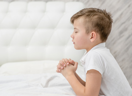 Young boy praying in bedroom before going to bed. Empty space for text.