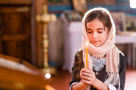 Little girl with a candle prays in church with eye closed.