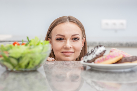 Happy pregnant girl chooses between donut and vegetable salad. Stock Photo