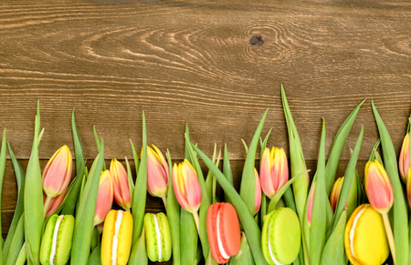 Tulips  with macaroons over brown wooden background. Backdrop with empty space for text. 版權商用圖片