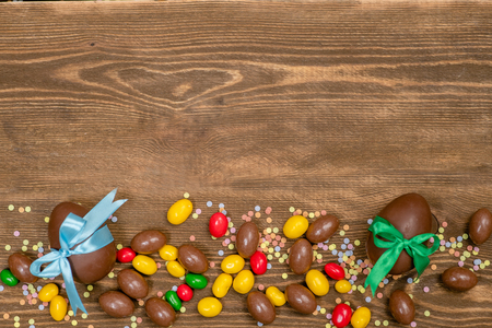 Chocolate Easter eggs and sweets over brown wooden background. Empty space foe text.