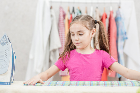 Little girl ironing clothes using iron on ironing board after laundry at home.