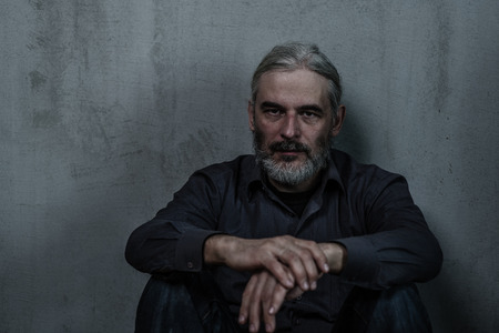 Portrait of a homeless man with a gray hair on dark background. Empty space for text.