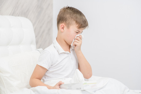 Sick child on bed and blowing his nose in tissue. Standard-Bild