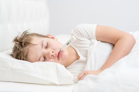 Chory chłopiec śpi pod kocem z termometrem w ustach.