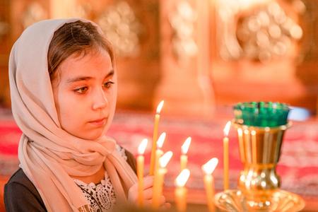 Kleines Mädchen mit Kerze in der Kirche. Standard-Bild