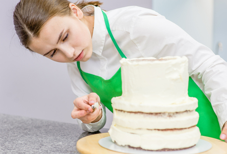 confectioner makes a wedding cake with white cream  using a  cooking spatula.