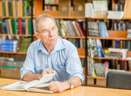 Anciano pensativo en la biblioteca mirando a otro lado. Foto de archivo