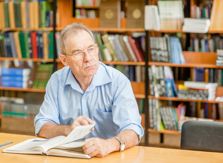 Pensive old man in the library looking away. Reklamní fotografie