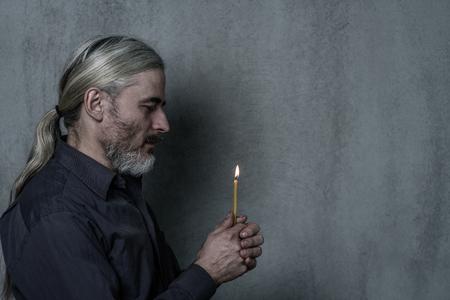 Les mains d'un homme âgé tiennent un fond sombre de Candleon dans le profil. Espace vide pour le texte.
