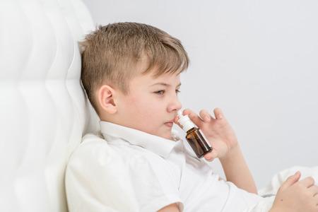 Ill boy with flu using nose spray.
