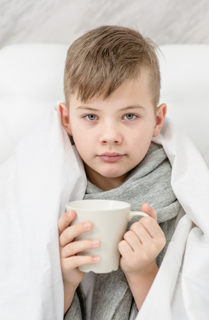 Sick boy  with warm scarf sitting on the bed and holds cup. 免版税图像