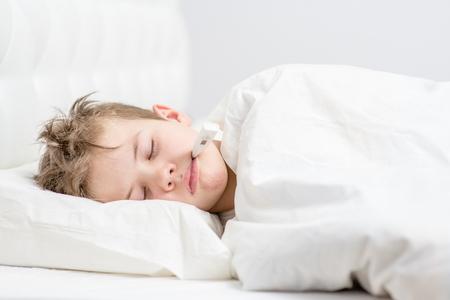 Un garçon malade dort sous une couverture avec un thermomètre dans la bouche.