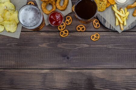 Mix of snacks with beer on dark wooden background. Top view, Empty space for text.