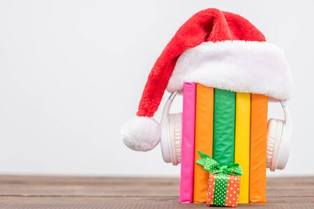 Multicolored books and white  headphones with red christmas hat and gift box on white background. Empty space for text.
