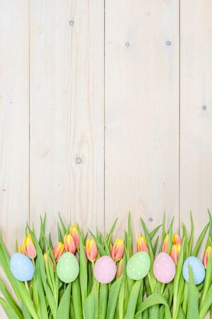 Tulips and easter eggs on light wooden background. Empty space for text.