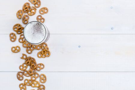 Beer with pretzels on wooden background. Top view. Empty space for text.