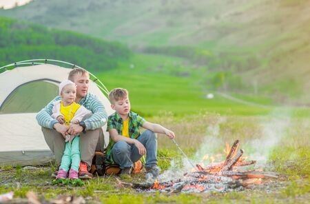 Happy family around by the campfire. Imagens