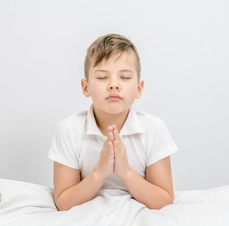 Young boy  praying in bedroom before going to bed. Standard-Bild