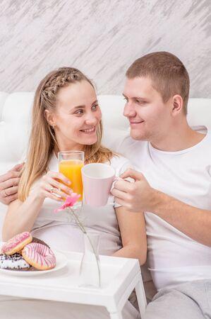 Romantic happy couple having breakfast on the bed.