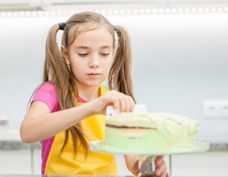 Little girl making biscuit cake with white cream  using a  cooking spatula.