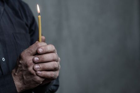 Old mans hands hold a candleon dark background. Empty space for text. Imagens