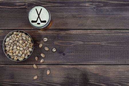 Beer and pistachios on dark wooden background. Top view. Empty space for text.