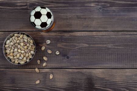 Beer with a football on a beer foam and pistachios on dark wooden background. Top view. Empty space for text.