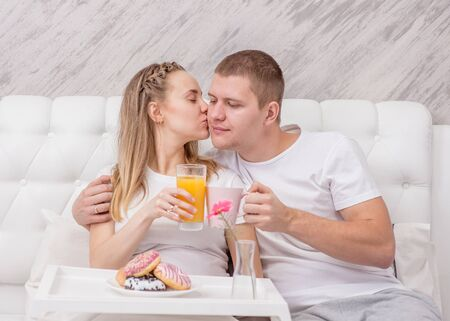 Happy young family at bedroom. Romantic happy couple having breakfast at home.