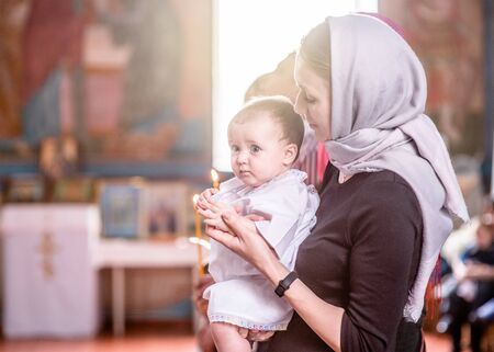 Woman baptizes a child in church. Stock Photo