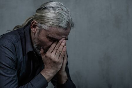 Senior man covering face and crying on dark background. Empty space for text.