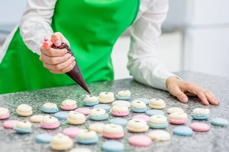 Closeup chef with confectionery bag squeezing cream filling to macarons shells.