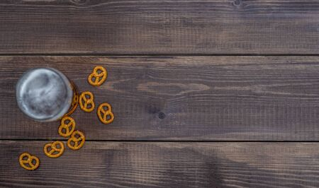 Beer with pretzels on dark wooden background. Top view. Empty space for text.