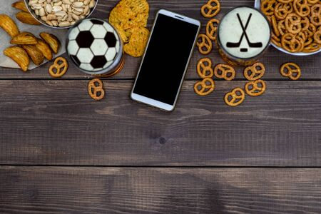 Varied snacks and beer with silhouettes of hockey sticks and soccer ball on beer foam and smartpnone on dark wooden background. Internet delivery concept. Top view. Empty space for text.